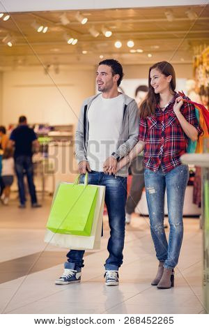Young shopping couple in shopping center with shopping bags