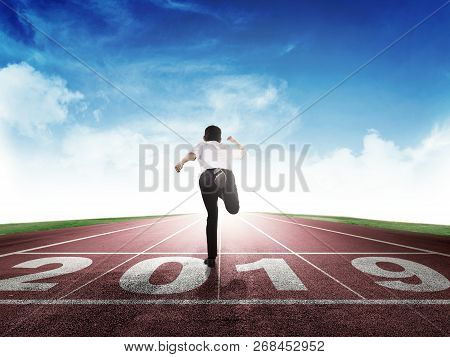 Rear View Of Asian Businessman Running On Running Track With 2019 Number On Start Line. Happy New Ye