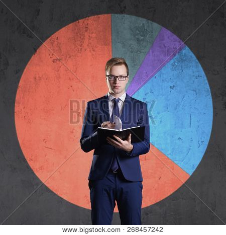 Business Man With Organizer Standing On A Diagram Background. Business, Office, Career, Concept.