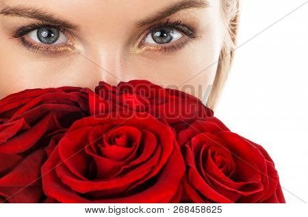 Beautiful young woman with red roses. Focus on eyes.