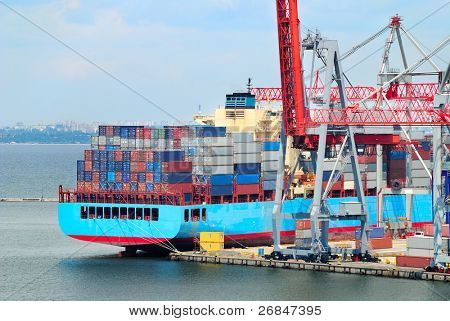 View on trading seaport with cranes, cargoes and the ship