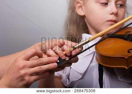 The Teacher Corrects The Hands Of The Little Girl Teaching The Violin