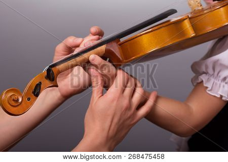 Hands Of A Teacher Of Playing The Violin Correct Little Pupil On A Gray Background
