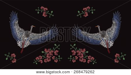 Flying Asian Crane And Blooming Flowers Embroidered With Colorful Threads On Black Background. Embro