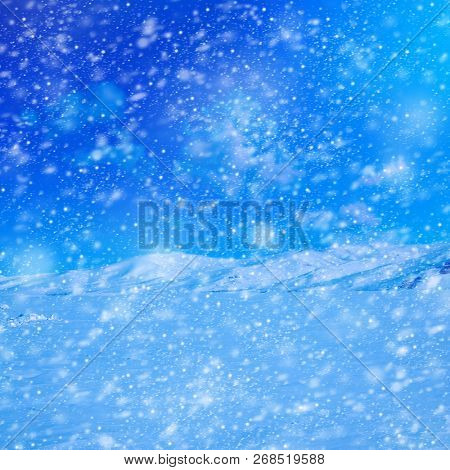 Snow covered empty frozen landscape of mountainside over blue sky with clouds
