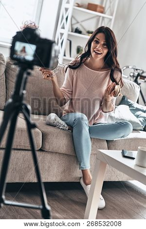 Modern Vlogger. Beautiful Young Woman Holding Beauty Products And Smiling While Making Social Media