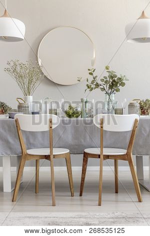 Two White Chairs Standing By The Table With Fresh Plants And Glass Vessels In The Photo Of Bright Di