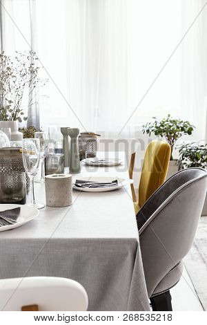 Real Photo Of Table With Dinnerware, Candle And Grey And Yellow Chair Standing In Bright Dining Room