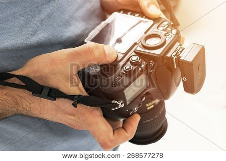 Digital Single Lens Reflex Camera In Male Hands. Photographer Shooting Hands Close Up. Man Photograp