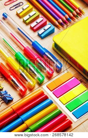 Group Of School Supplies And Notebooks On Wooden Table