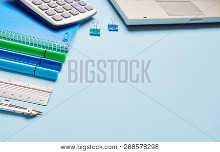 On A Blue Background, A Laptop And A School Stationery