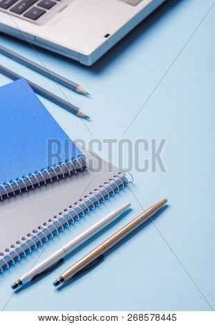 Pencils Next To Notebooks And Pens On A Blue Background