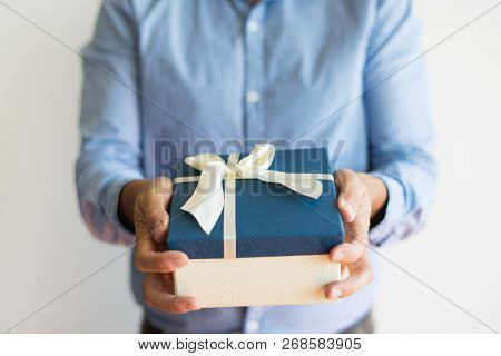 Close-up Of Unrecognizable Man Giving Gift Box To Camera. Man In Casual Shirt Presenting Christmas P