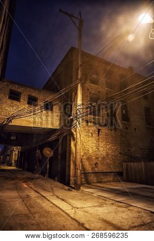 Dark and scary downtown urban city street alley scene with an ee poster