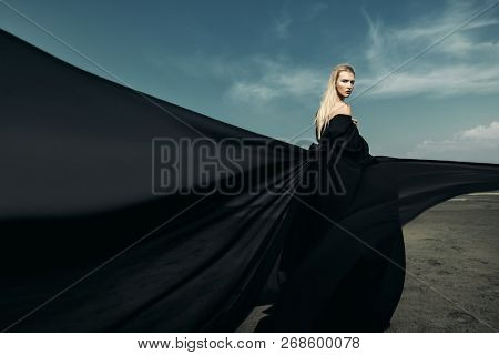 A portrait of a beautiful gothic woman in long black dress posing outdoor. Beauty, fashion.