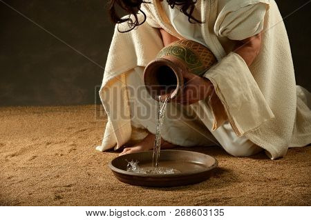 Jesus pouring water from a jar before washing his disciples feet