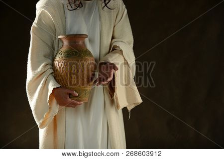Jesus holding a jag of water standing up with a dark background