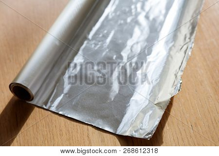 Aluminum Foil Roll On Wood Table, Close Up.