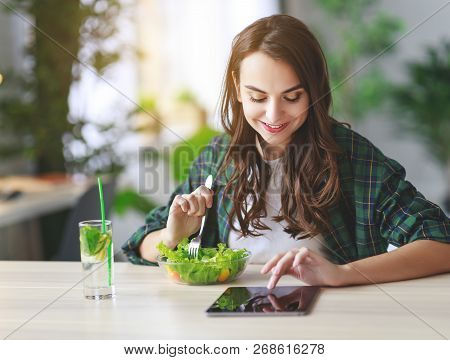 Healthy Eating. Happy Young Girl Eating Salad With Tablet Pc In The Morning In Kitchen