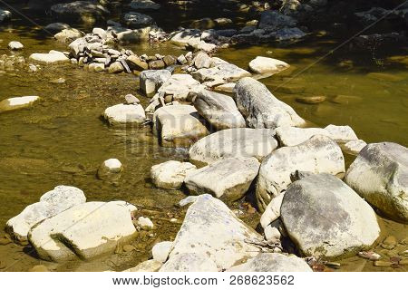 The Mountain River. Shallow Mountain River, Water Flows Through The Rocks. Rocks In The River Water.