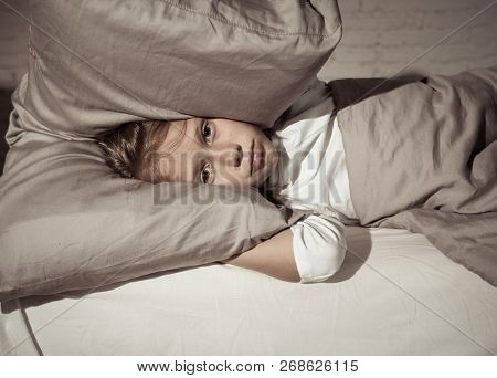 Little Girl Having Trouble Sleeping At Night Holding Pillow Covering Her Head And Ears Upset
