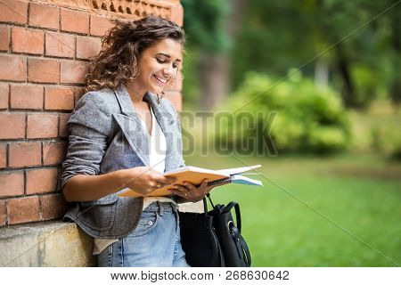 Young Caucasian College Student With Book In College Campus. University Student Going To College.