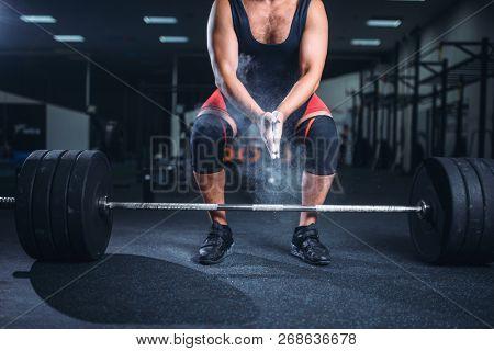 Powerlifter rubs his hands with talcum powder