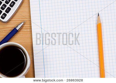 checked notepad and pencil at wood