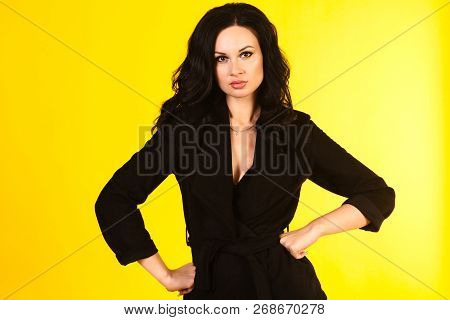Business Woman In A Black Suit, Isolated On Yellow Background.