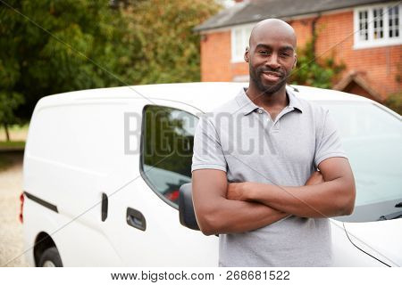 Young black adult tradesman standing next to his white van, close up, close up