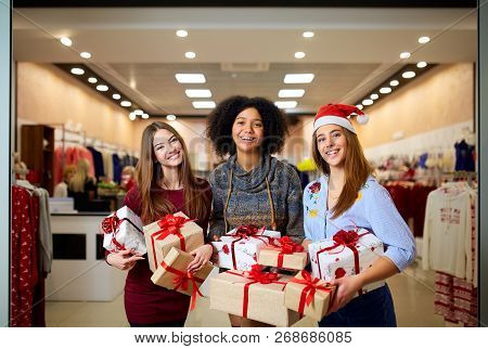 Three Mixed Race Women With Gift Boxes In Hands At Store. Multi Ethnic Girls Smiling With Presents O