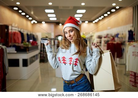 Happy Young Blonde Woman In Christmas Hat Holding Credit Card And Colorful Shopping Bags, Looking At