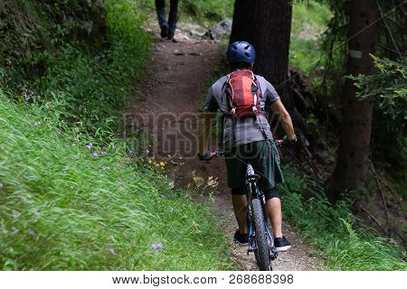 Cyclist In Red Riding The Bike On The Autumn Rocky Trail At Sunset. Extreme Sport And Enduro Biking