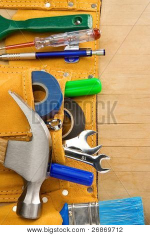 tools and instruments in leathern belt on wooden texture