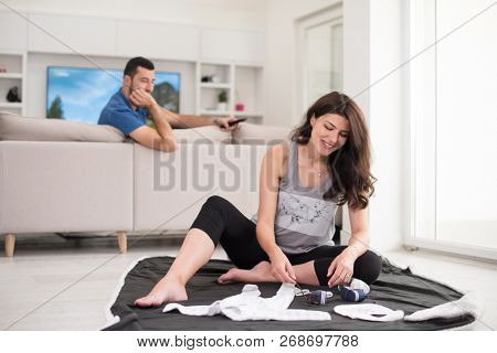 a happy pregnant couple checking a list of things for their unborn baby at home on the floor