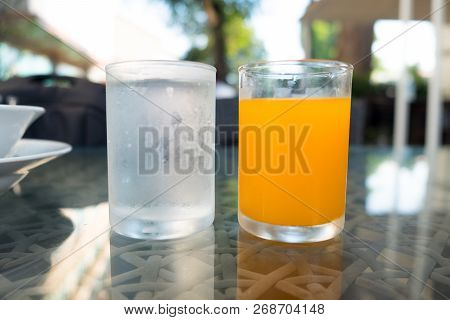 Glass Of Water And Orange Juice On The Breakfast Table