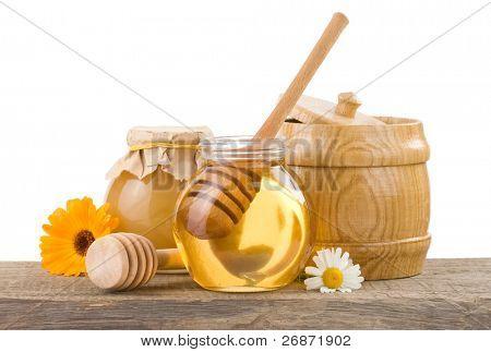 jar of honey and stick isolated on white background