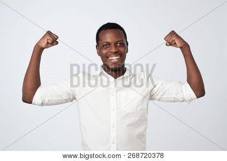 Portrait Of A Strong Young African Man In White Shirt Flexing Biceps