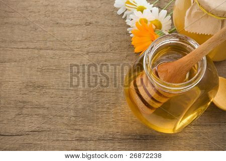 jar of honey and flowers on wood background
