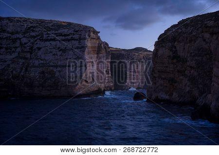 Cliffs In Island Of Gozo (dwejra Bay) At Dusk. On Right Side Fungus Rock. Winter, Malta.