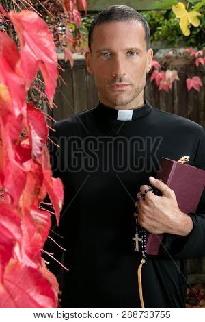 Good Looking Priest Stands In Garden Holding His Bible Next To Virginia Creeper Ivy