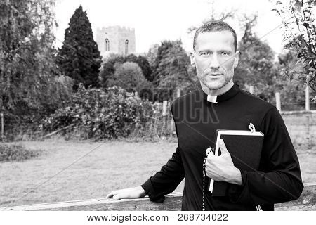 Handsome Priest Standing Next To Country Gate While Holding His Bible With Church And Field In Backg