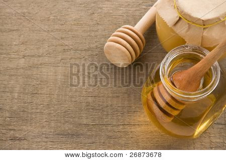jar and pot of honey with stick on wood background