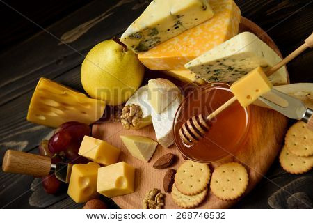 Various Types Of Cheese On A Rustic Wooden Table