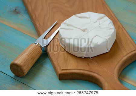 Cheese Camembert Or Brie On Blue Wooden Background