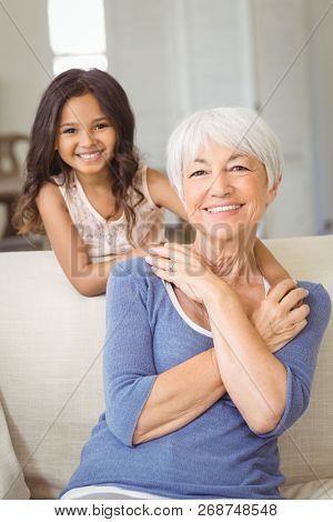 Portrait of smiling granddaughter embracing her grandmother in living room at home