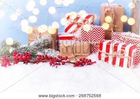 New Year Decorations. Wrapped Christmas Presents, Fur Tree Branches,  Berries  Against Blue Textured