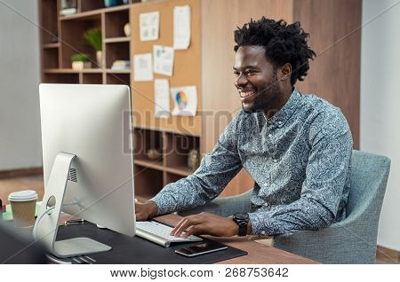 Portrait of african american businessman using computer at desk. Handsome employee enjoying work in modern office. Smiling creative business man feeling happy about positive report.