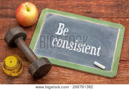 Be consistent concept -  slate blackboard sign against weathered red painted barn wood with a dumbbell, apple and tape measure poster