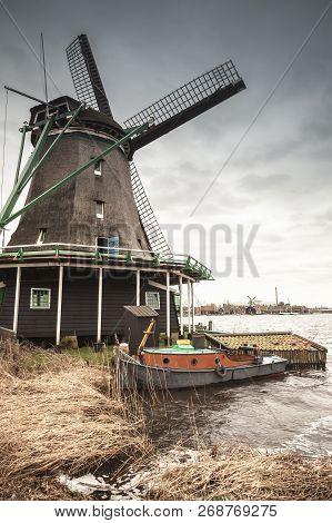 Windmill Under Dark Cloudy Sky On Zaan River Coast, Zaanse Schans Town, Popular Tourist Attractions